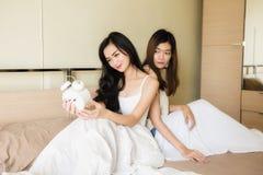 Asiatiska kvinnapar ser klockan på säng Arkivbild