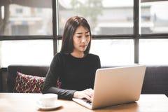 Asiatiska kvinnor för affär som använder minnestavladatoren för att arbeta med finansiella data i arbetsutrymmet äganderätt för h royaltyfria bilder