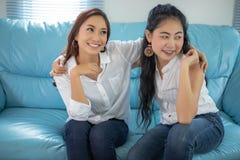 Asiatiska kvinnor f?r livsstilst?ende av b?sta v?n - le som ?r lyckligt p? soffan p? vardagsrum royaltyfri bild