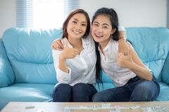 Asiatiska kvinnor f?r livsstilst?ende av b?sta v?n - le som ?r lyckligt p? soffan p? vardagsrum royaltyfri fotografi