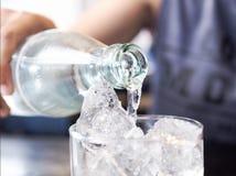 Asiatiska kvinnor häller rent dricksvatten i isexponeringsglas royaltyfri fotografi