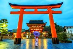 Asiatiska kvinnor i traditionella japanska kimonon på Fushimi Inari förvarar i Kyoto, Japan royaltyfri bild