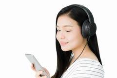 Asiatiska kvinnor lyssnar till musik från svart hörlurar arkivbild