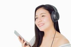 Asiatiska kvinnor lyssnar till musik från svart hörlurar I ett bekvämt och bra lynne royaltyfri fotografi