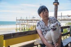 Asiatiska kvinnor och hund på stranden och havet när lopp arkivfoto