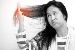 Asiatiska kvinnor ser skadat hår Royaltyfria Foton