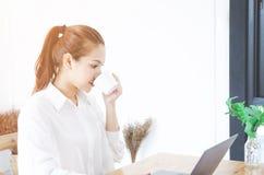 Asiatiska kvinnor som bär en vit skjorta, är arbeta och läppja kaffe royaltyfri bild