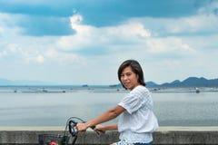 Asiatiska kvinnor som cyklar på vägen på den Krasiew fördämningen, Supanburi arkivfoto