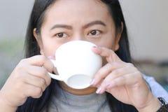 Asiatiska kvinnor som dricker varmt kaffe i en vit kopp arkivbilder