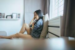 Asiatiska kvinnor som hemma sitter på sovrum, kvinnlig känslig huvudvärk och förvirrat problem i personligt liv, det att använda  arkivbilder