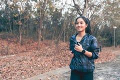 Asiatiska kvinnor som kör och joggar under utomhus- på vägen parkerar in royaltyfria bilder