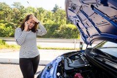 Asiatiska kvinnor som kallar för hjälp, når avbrott ner av bilengin Royaltyfri Bild