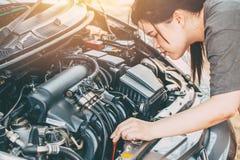 Asiatiska kvinnor som kontrollerar motorn för bilen LPG för, går turen royaltyfri foto