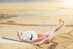 Asiatiska kvinnor som kopplar av i h?ngmattasommarferie p? stranden royaltyfri fotografi