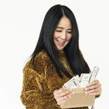 Asiatiska kvinnor som ler hållande pengarlyckabegrepp arkivfoto