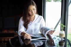 Asiatiska kvinnor som ler och läser en bok för avkoppling på kaffekafét fotografering för bildbyråer