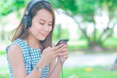 Asiatiska kvinnor som lyssnar till musik med hörlurar i trädgården arkivfoton