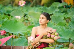 Asiatiska kvinnor som mot efterkrav sitter på trälotusblomma för fartyg arkivfoto