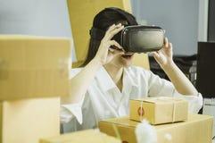 Asiatiska kvinnor startar upp små och medelstora företagägaren, använder vr för att meddela, med kartongen för packande produkter arkivbild