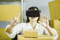 Asiatiska kvinnor startar upp små och medelstora företagägaren, hand genom att använda vr för att meddela, med kartongen för pack arkivfoto