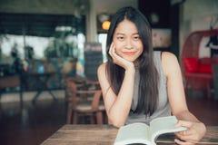 Asiatiska kvinnor tycker om leendeläseboken i ferie som ser kameran arkivfoto