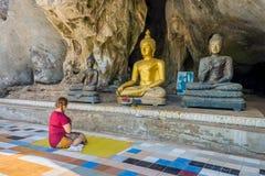 Asiatiska kvinnor vallfärdar dyrkaner Buddhastatyerna på grottan av Wat Tham Khao Wong Royaltyfri Bild