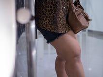 Asiatiska lår av feta kvinnor Hon bär kortslutningar och lång-muffa skjortor för att se överskottfett fotografering för bildbyråer
