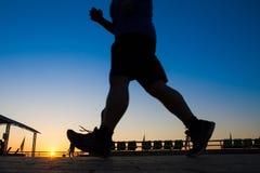 Asiatiska män är konturn som joggar på en hastighet i aftonen Royaltyfri Fotografi