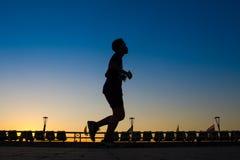 Asiatiska män är konturn som joggar på en hastighet i aftonen Arkivbild
