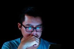Asiatiska män använder telefonen eller minnestavlan med ett blått ljus i mörkret Arkivbilder