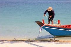 Asiatiska män binds ett rep med lång-svansen fartyget på stranden Arkivbilder
