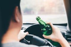 Asiatiska män bryter trafikreglerna, genom att rymma en flaska av öl och att dricka stundkörning arkivfoto