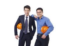 Asiatiska män med den orange säkerhetshatten Arkivbilder