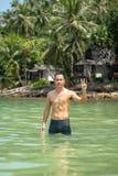 Asiatiska män som simmar i havsbakgrunden, vaggar och träd arkivbilder