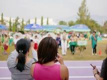 Asiatiska mödrar som håller ögonen på och tar foto av deras barn som deltar i en sportdaghändelse på skola fotografering för bildbyråer