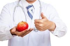 Asiatiska manliga doktorstummar upp med äpplet Arkivbild
