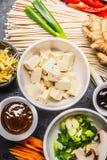 Asiatiska matingredienser: tofu, nudlar, ingefära, klippta grönsaker, grodd, salladslök och hoisinsås för smaklig matlagning royaltyfri bild