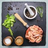 Asiatiska matlagningingredienser med ny liten räka i en liten stekpanna, örter, peppar på stensvartbakgrund Royaltyfri Fotografi
