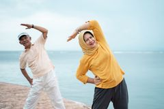 Asiatiska muslim för par som tillsammans sträcker och övar fotografering för bildbyråer