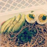 Asiatiska nudlar för sunt mål med avokadot och det kokta ägget med persilja royaltyfri bild