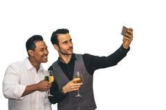 Asiatiska och caucasian män dricker champagne och selfie till cel royaltyfria bilder