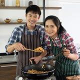 Asiatiska par är lyckliga att laga mat tillsammans i morgonen royaltyfria foton