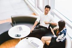 Asiatiska par eller coworkers som har kaffeavbrottet, medan arbeta på bärbar datordatoren på kafét, coffee shop eller det moderna royaltyfri bild