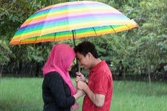 Asiatiska par för utomhus- muslim i regnet Arkivfoto