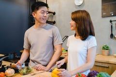 Asiatiska par förbereder mat tillsammans Den härliga lyckliga asiatiska mannen och kvinnan lagar mat i köket Arkivbild