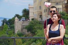 Asiatiska par gör selfie med en smartphone på en pinne på synvinkeln i Monaco Arkivfoto