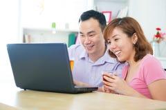 Asiatiska par genom att använda anteckningsboken Arkivbild