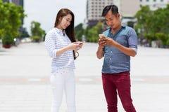 Asiatiska par genom att använda det smarta telefonmeddelandet för cell Arkivbilder