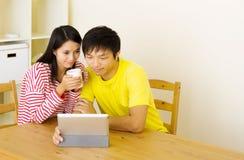 Asiatiska par genom att använda minnestavlan tillsammans Arkivbild