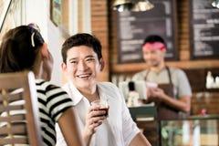 Asiatiska par i kafét som flörtar, medan dricka kaffe Arkivfoto